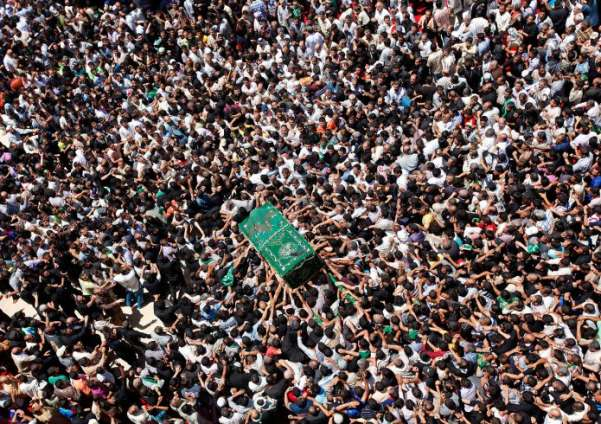 Shiite pilgrims carry a symbolic coffin at the holy shrine of the Imam Moussa al-Kadhim shrine in Baghdad, Iraq. Hundreds of thousands of Shiite pilgrims are flocking to the shrine to commemorate the death of the revered eighth century saint, snarling traffic and sending security forces to the streets to protect the worshipers. Hadi Mizban—AP