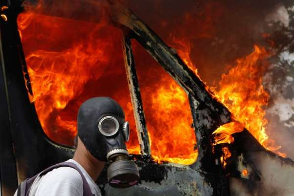 A gas-masked protester walks by a burning van during demonstrations against austerity measures in Athens. As Greece teeters on the brink of bankruptcy, its Parliament voted in favor of a package of spending cuts, tax hikes and privatization that was a prerequisite for a critical bailout. Yannis Behrakis—Reuters
