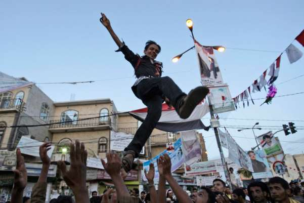 Anti-government protesters reach to catch a youth, after throwing him in to the air while celebrating President Ali Abdullah Saleh's departure to Saudi Arabia, in Sanaa, Yemen. A cease-fire in Yemen's capital was at risk of unraveling Monday as regime supporters opened fire on opposition fighters in renewed clashes that killed at least six. The violence raises fears over the potentially explosive situation after the wounded President Ali Abdullah Saleh left the country, creating a deep power vacuum.Hani Mohammedi—AP
