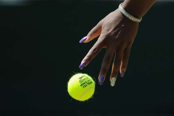 US player Serena Williams bounces the ball as she plays against Romania's Simona Halep in a Women's Singles match at the 2011 Wimbledon Tennis Championships at the All England Tennis Club, in southwest London. Carl de Souza—AFP/Getty Images
