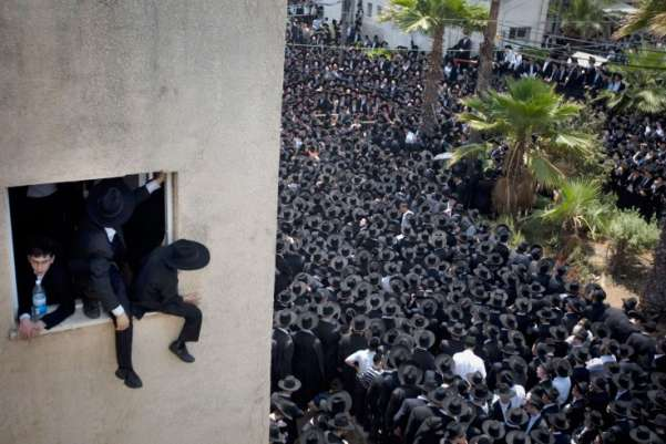 Ultra-Orthodox Jewish youth strain for a view as thousands gather around the body of Rabbi Michel Yehuda Lefkowitz, a Lithuanian Orthodox leader, during his funeral on June 28 in Bnei Brak, Israel. Ariel Schalit—AP