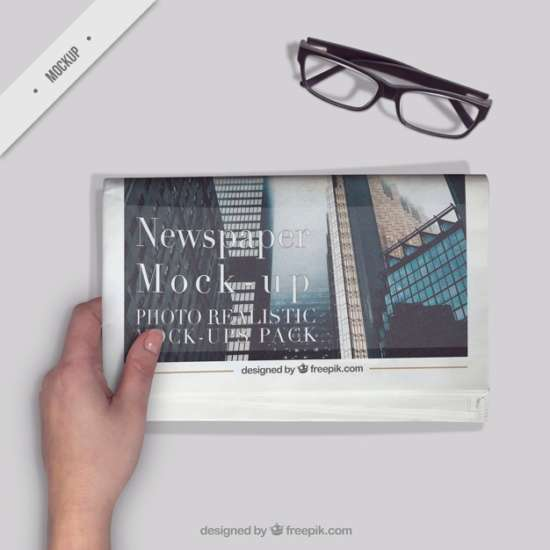 person_reading_a_newspaper_with_a_glasses_on_the_desktop